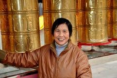 Pengzhou, Cina: Donna sorridente con i tamburi tibetani della ruota di preghiera Immagini Stock