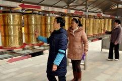 Pengzhou, Cina: Donne che filano i tamburi tibetani della ruota di preghiera Fotografia Stock