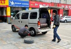 Pengzhou, Cina: Gomma di automobile cambiante dell'uomo Immagini Stock