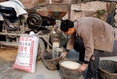 Pengzhou, Cina: Granuli sbuccianti del riso dell'uomo immagini stock