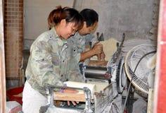 Pengzhou, Cina: Operai che producono la pasta della tagliatella Immagini Stock