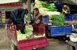 Pengzhou, Cina: Uomini che caricano prodotti Fotografia Stock