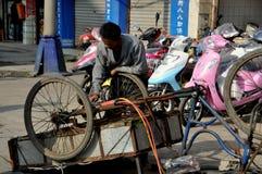 Pengzhou, Cina: Uomo che ripara il carrello della bicicletta Fotografia Stock Libera da Diritti