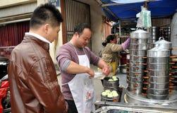 Pengzhou, Cina: Uomo che vende le polpette di Bao Zi Fotografia Stock Libera da Diritti