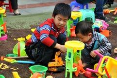 Pengzhou Kina: Barn på spelrum med Toys Arkivbilder