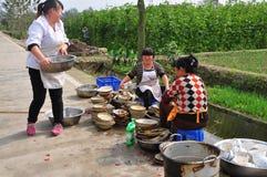 Pengzhou Kina: Kvinnor som tvättar disk Fotografering för Bildbyråer