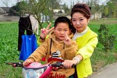 Pengzhou Kina: Moder och son på mopeden Royaltyfri Fotografi