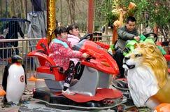 Pengzhoul, China: Kids at Amusement Park. Children and adults having fun on a water gun jungle amusement park ride in Pengzhou Park in Pengzhou, China Royalty Free Stock Photos