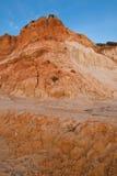 Penhasco alaranjado vermelho da rocha do solo no falesia do Sandy Beach no céu azul do por do sol Imagens de Stock Royalty Free