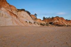 Penhasco alaranjado vermelho da rocha do solo no falesia do Sandy Beach no céu azul do por do sol Imagens de Stock
