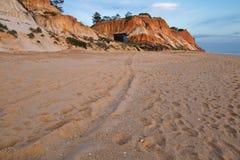 Penhasco alaranjado vermelho da rocha do solo no falesia do Sandy Beach no céu azul do por do sol Imagem de Stock Royalty Free