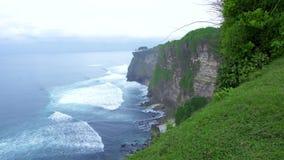 Penhasco da montanha no litoral e em espirrar ondas do mar Montanha de surpresa do penhasco da paisagem e ilha rochosa no oceano  filme