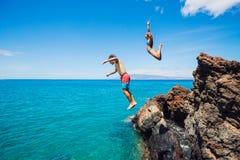 Penhasco dos amigos que salta no oceano Imagem de Stock Royalty Free