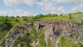 Penhasco e caverna rochosos grandes nela A câmera está aproximando-se de longe vídeos de arquivo
