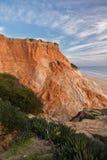 Penhasco vermelho da rocha da pedra do solo no litoral atlântico no falesia da praia no céu azul Imagens de Stock