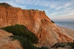 Penhasco vermelho da rocha da pedra do solo no litoral atlântico no falesia da praia no céu azul Fotos de Stock Royalty Free