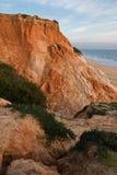 Penhasco vermelho da rocha da pedra do solo no litoral atlântico no falesia da praia no céu azul Fotografia de Stock Royalty Free