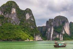 Penhascos da pedra calcária da baía de Halong com o barco de pesca verde tradicional, herança natural do mundo do UNESCO, Vietnam fotos de stock