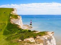 Penhascos de giz brancos e farol principal Beachy, Eastbourne, Sussex do leste, Inglaterra imagem de stock