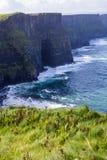 Penhascos de Moher no oceano de Alantic na Irlanda ocidental com as ondas que golpeiam contra as rochas foto de stock