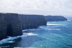 Penhascos de Moher no oceano de Alantic na Irlanda ocidental com as ondas que golpeiam contra as rochas imagens de stock royalty free