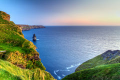 Penhascos irlandeses de Moher no por do sol Fotografia de Stock Royalty Free