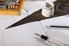 A penholder  with a pen and a simple pencil lie on an open notebook. View from above. Close-up. Royalty Free Stock Photography