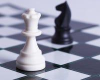 Penhor branco e cavaleiro preto na placa de xadrez Imagem de Stock