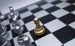Penhor da xadrez do ouro na frente da tropa branca Imagens de Stock