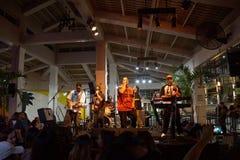 Peni Dean ledningssångare som sjunger in i mic som musikband, sitter fast på etapp Royaltyfri Fotografi