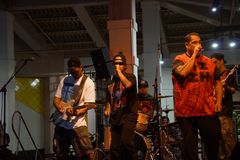 Peni Dean ledningssångare som sjunger in i mic som musikband, sitter fast på etapp Arkivbild