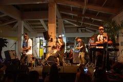 Peni Dean ledningssångare som sjunger in i mic och dans som musikbanddriftstopp på Royaltyfri Bild