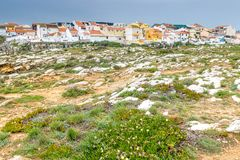 Peniche, Portugal. Rocky coast at Peniche, Portugal with small residential houses clustered in the background royalty free stock images