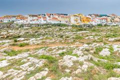 Peniche, Portugal. Rocky coast at Peniche, Portugal with small residential houses clustered in the background stock photography
