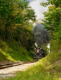 Approaching steam train. PENINSULA, OH - SEPTEMBER 17, 2917: The NKP-765, one of the largest steam locomotives still in existence, approaches with a full billow Royalty Free Stock Photo