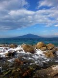 Vesuvius, seen from the Sorrento coast. In the foreground a cliff with the foam produced by the waves of the sea stock images