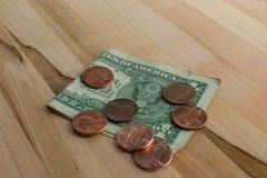 Peniques de los E.E.U.U. en billete de dólar doblado foto de archivo