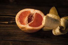 Penis and vagina, banana with yellow peel in red grapefruit. On wooden background, sex and sexual intercourse, fruit love, vitamin and dieting, healthy food Royalty Free Stock Images