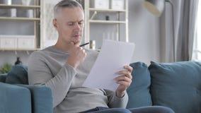 Penisve Gray Hair Man Reading Agreement, s'asseyant sur le sofa banque de vidéos
