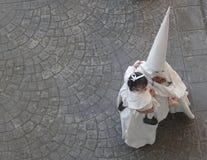 Penitent идет в улицу с младенцем в шествии святой недели стоковые фото