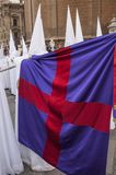 Penitent of the brotherhood of. `La Paz` carrying a flag Royalty Free Stock Images