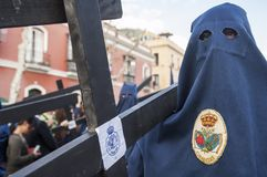 Penitent of the brotherhood of. `El Baratillo` in formation during the processional station carrying  a cross Royalty Free Stock Photos