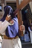 Penitent of the brotherhood of. `La Exaltacion` in formation during the processional station carrying  a cross Stock Photos