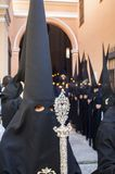 Penitent of the brotherhood of. `Santa Marta` in formation during the processional exit carrying badge Royalty Free Stock Photo