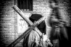 Penitent carrying wooden cross during station of penance in Holy Week. Spain Stock Photography