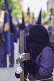 Penitent dressed in purple tunic of velvet resting on wooden cro Stock Photos