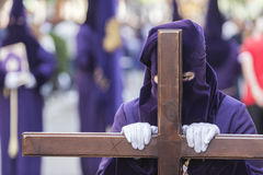 Penitent dressed in purple tunic of velvet resting on wooden cro Royalty Free Stock Photos