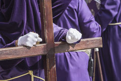 Penitent dressed in purple tunic of velvet resting on wooden Stock Images