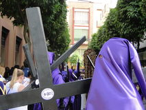 Penitent nazarene. Nazarero doing penance with a cross over his shoulders in the holy week of Seville in Andalusia, south of Spain Royalty Free Stock Photography