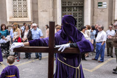 Penitent posed holding his cross during Holy week procession Stock Images
